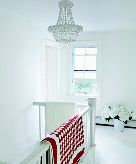 a white stairway landing with window chandelier and red and white quilt