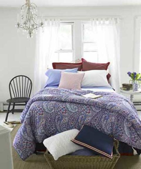 a bed with layered patterns paisley stripes in red white and blue colors
