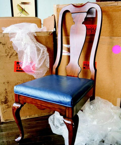a wooden chair with pleather cushion surrounded by boxes and bubble wrap