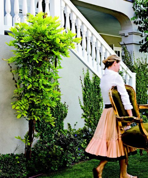 shop owner annette tatum outside her home in a taffeta skirt carrying a chair