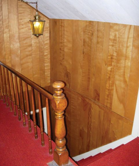 a shot of a before stairway with red carpet and faux wood paneling