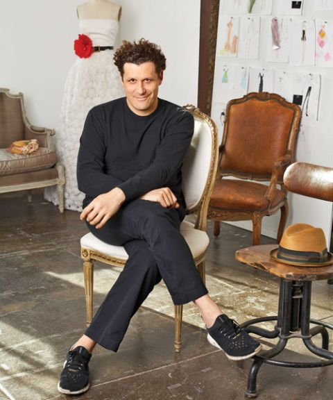 fashion designer isaac mizrahi in his design studio with leather chairs and dress