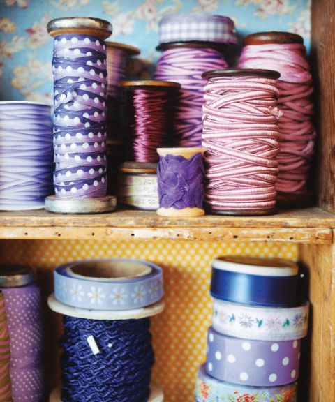 spools of lavender and purple ribbon on wooden shelves