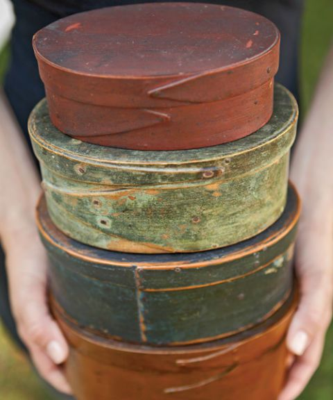 stack of shaker pantry boxes with original paint in rust and green colors
