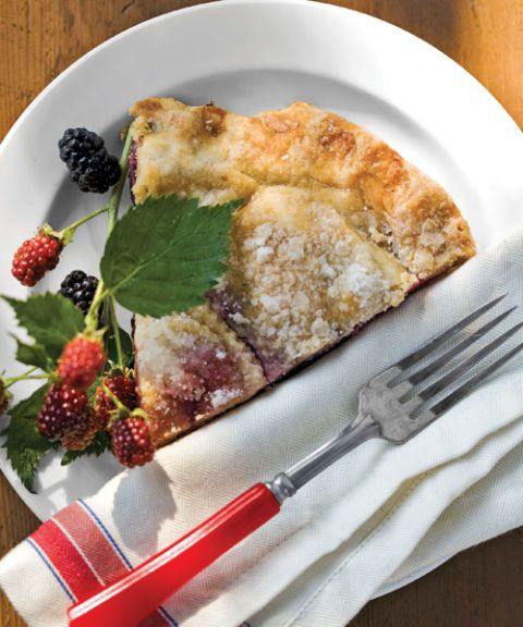 a slice of berry pie on white plate with fork and napkin