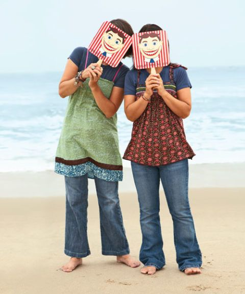two women holding masks in front of their faces on the beach