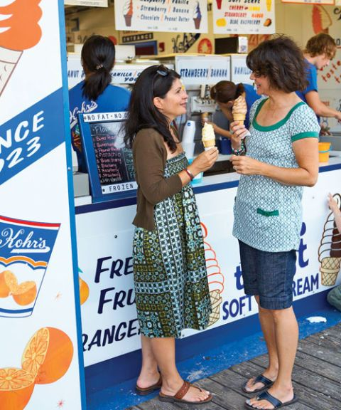 two women holding ice cream cones in front of a shop