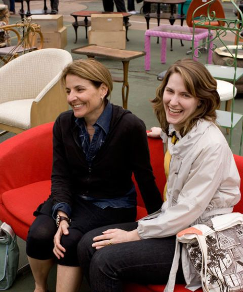 two women sitting on a red sofa