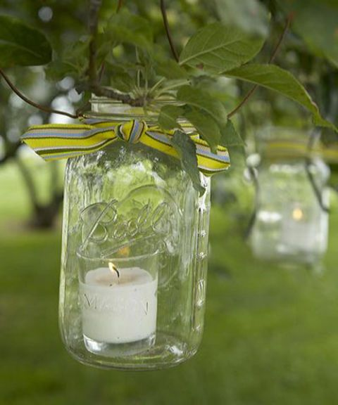 mason ball jar with candle inside hanging from tree