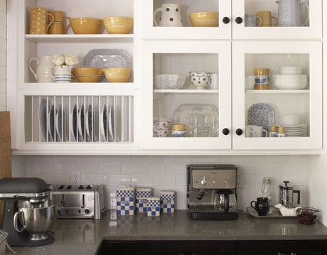 glass front cabinets with black door knobs and open plate rack