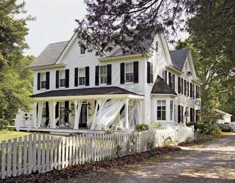 large white farmhouse with black shutters and a white picket fence