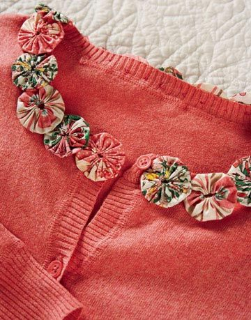 a bright coral cardigan accented with fabric yo-yos at the collar