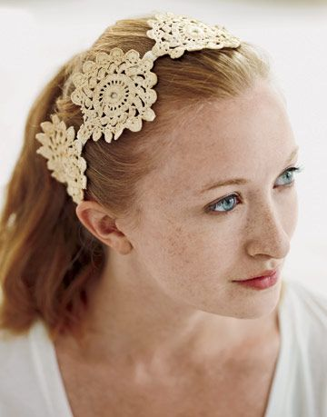 an elastic headband with off-white doilies sewn to it
