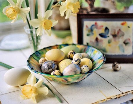 speckled quail and duck eggs in a paint-splattered ceramic bowl with daffodils