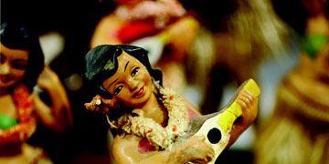 a vintage hawaiian hula girl souvenir doll with grass skirt and ukulele