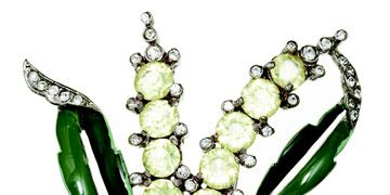 a flower pin with white rhinestones and green leaves