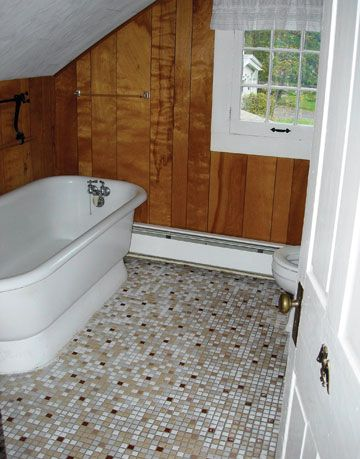 bathroom with wood-paneled walls and sloping ceiling