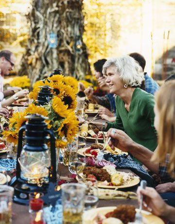 guests eating at an outdoor table with sunflowers and lanterns