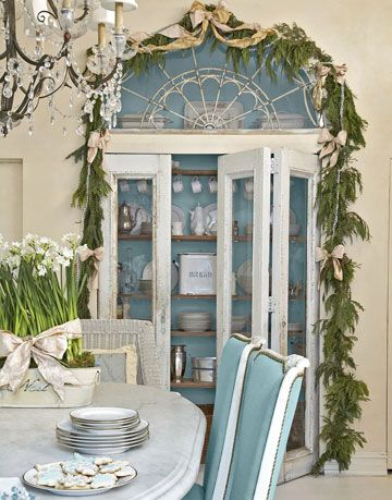 blue painted pantry with glass doors behind a table
