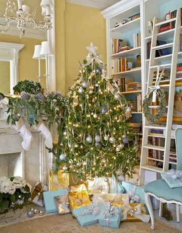 blue and white bookshelves with ladder next to a decorated christmas tree