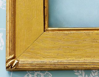 the corner of a gold wood picture frame