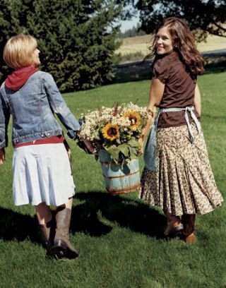 two women holding a bucket of flowers
