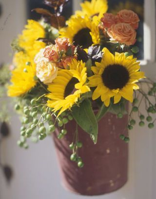 sunflowers and roses in a flower pot