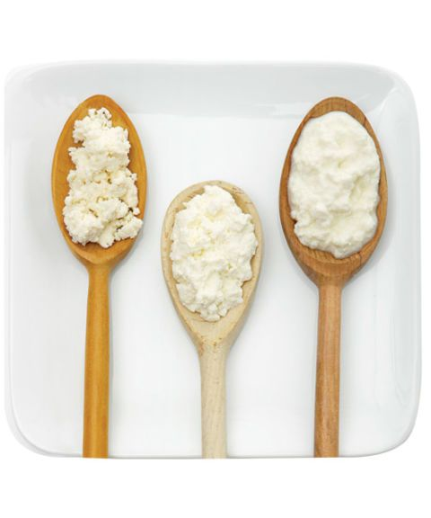 three different kinds of ricotta on wooden spoons on a square plate