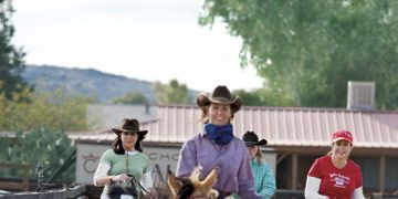 woman on horses in a corral
