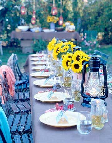 long table with place settings and sunflower centerpieces