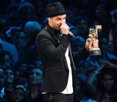 Face, Microphone, Hat, Music artist, Trophy, Suit, Fashion, Facial hair, Sun hat, Audience,