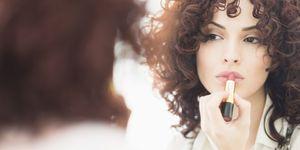 Vrouw doet lippenstift op