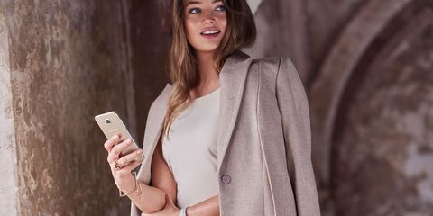 Hairstyle, Sleeve, Skin, Shoulder, Coat, Outerwear, Collar, Mobile phone, Blazer, Portable communications device,