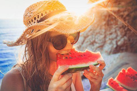 vrouw met hoed watermeloen strand