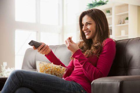 Vrouw kijkt tv op bank met popcorn