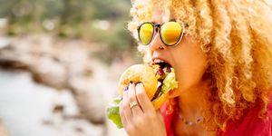 vrouw met krullen eet hamburger