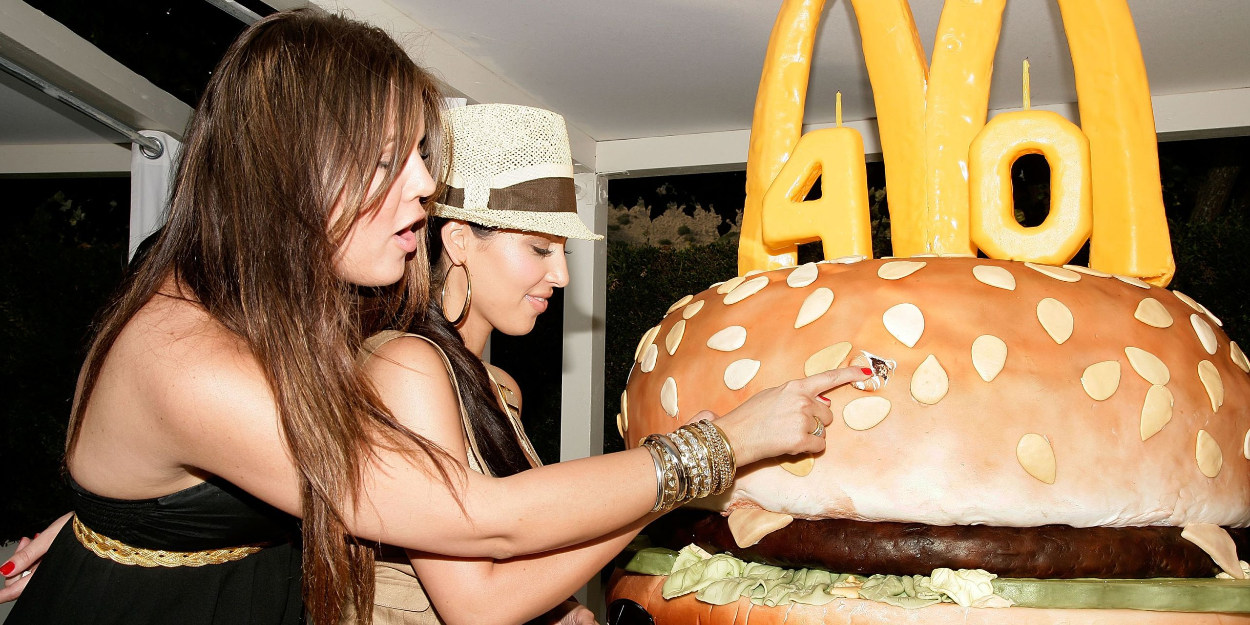 Kim and Khloé Kardashian cut into a giant Big Mac cake.