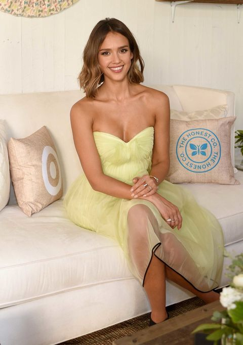 Clothing, Smile, Hairstyle, Strapless dress, Dress, Couch, Sitting, Beauty, Thigh, Living room,