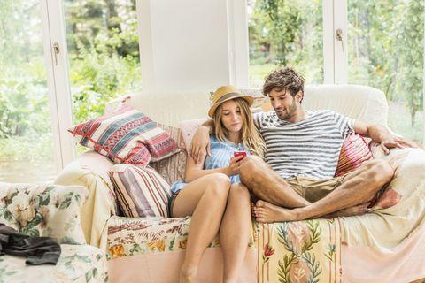 Human, Comfort, Hat, Sitting, Living room, Throw pillow, Bag, Beige, Thigh, Lamp,