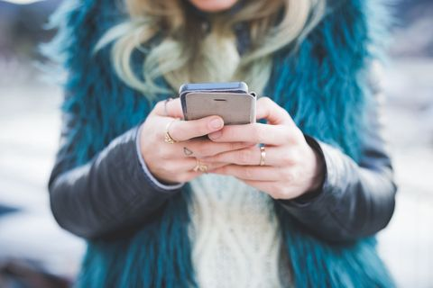 Cropped photo of woman with rings texting on smartphone