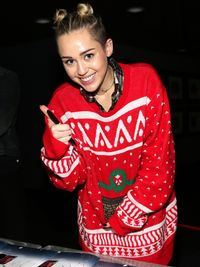 Taking a break from singing to sign some autographs at Jingle Ball, Miley rocked her own festive jumper! This oversized sweater looks just plain cozy.