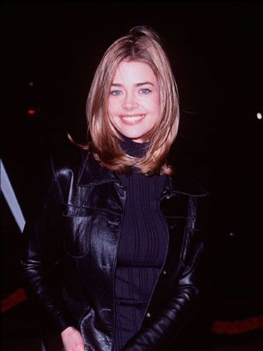 Denise wears a classic shoulder-length cut with a middle part.