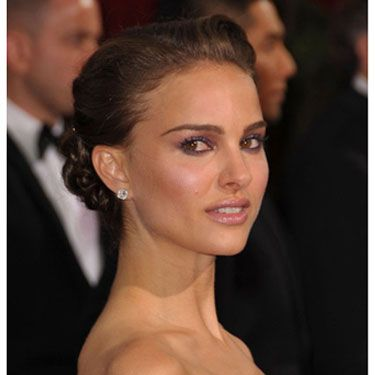 """Makeup artist Jeannine Lobell used Natalie Portman's orchid Rodarte dress as inspiration for this makeup effect. To get Natalie's deep purple smoky eyes use a pale pink shadow as a base and dark plum shadow in the crerases. Lobell recommends <a href="""" http://uma.chanel.com/-makeup-eyes-eye-shadows-irreelle-duo-silky-eyeshadow-duo-/product/MAEMU29D"""" target=""""_blank"""">Chanel Silky Eye Shadow Duo in Orient Express</a>. Finish off the eyes with lots of black liner and mascara. Next, blend a bright pink blush high on your cheekbones and swipe on a pale lavender lip gloss like <a href="""" http://uma.chanel.com/-makeup-lips-lip-gloss-levres-scintillantes-glossimer-/product/MALPR060"""" target=""""_blank""""> Chanel Glossimer in Galactic</a>. For a sexy, bronze sheen, apply bronzer to your arms, shoulders, and décolleté."""