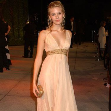 At the Vanity Fair Oscars party, Maggie glows with gold accessories and a Grecian-inspired dress.