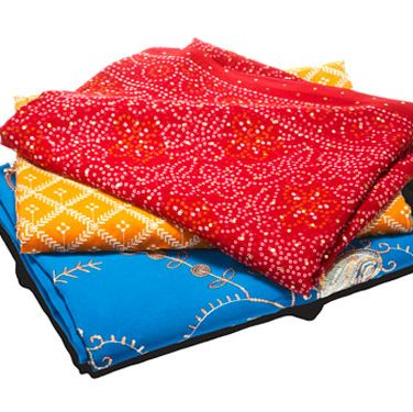 "Intricate ethnic cloths can add major flair. Place one at the foot of your bed, fold it in half over a curtain rod for a unique window shade, or drape one over a table as a runner. Go to <a href=""http://www.sarishop.com"" target=""_blank"">sarishop.com</a>, or visit a fabric store for a few yards of exotic-looking material.<br /><br /><i>Yellow sari, $12, and red sari, $20: India Sari Palace, Jackson Heights, N.Y., 718-426-2700&#x3B; blue sari: $30, Rahul, Jackson Heights, N.Y., 718-205-1987</i>"