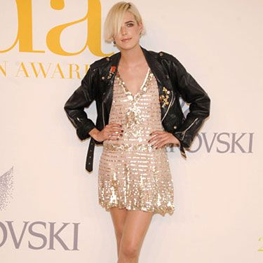 The model mixed black tie with her signature rocker style by adding black mini boots and a leather jacket to a sequin minidress.