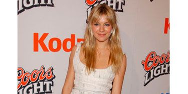 At the <i>Cold Mountain</i> premiere, Sienna stepped out in a quirky white chiffon dress that was short in the front and long in the back.
