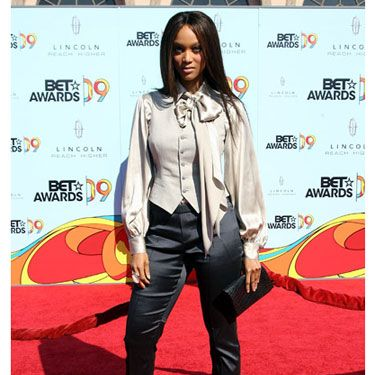 It takes a strong woman to make menswear sexy enough for the red carpet. Tyra pulled off the look in a champagne blouse, vest, black satin pants, and platform pumps.