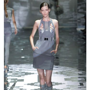The unusual cutouts and the silver material underneath give Gucci's otherwise classic sheath a racy, spacey look. Slick, pulled-back hair and clean, minimal makeup complement a sleek dress.