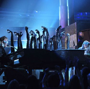 "After jumping into a stage furnace, Gaga emerged to sing a duet with Elton John from a double-sided piano with charred hands sticking out. Both covered in soot and wearing matching sequined sunglasses, Elton and Gaga sang a medley of her ""Speechless"" and his ""Your Song."" Elton even changed his lyric to sing, ""How wonderful life is with Gaga in the world."""